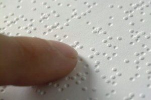 closeup of a fingertip on interpoint braille